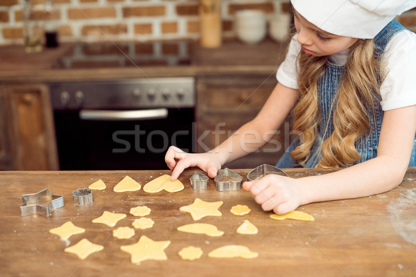 side view of little girl in chef hat making shaped cookies in