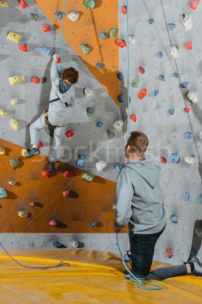Little boy climbing wall with grips Stock photo © LightFieldStudios