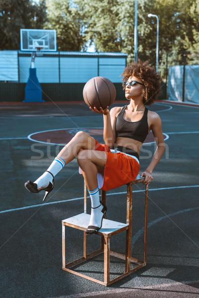 woman holding basketball at sports ground Stock photo © LightFieldStudios
