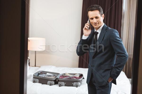 Empresário falante telefone quarto de hotel formal terno Foto stock © LightFieldStudios