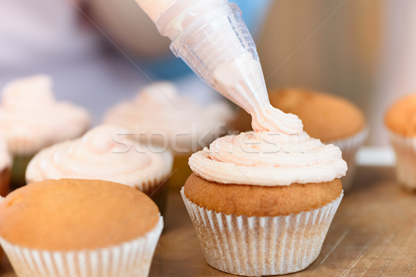 close up view of putting cream on cupcakes process Stock photo © LightFieldStudios