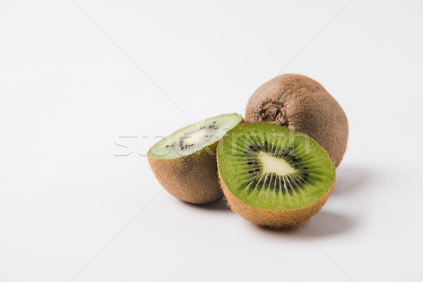 whole and halved kiwi laying on white background  Stock photo © LightFieldStudios