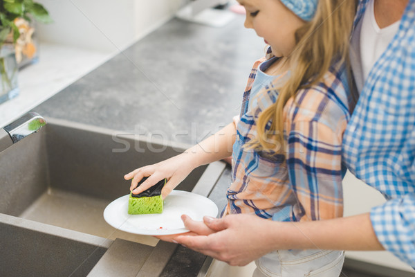 cropped shot of little daughter helping mother to wash dishes after dinner at home Stock photo © LightFieldStudios