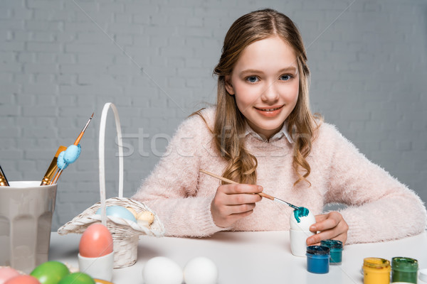 dorable happy girl painting easter egg and smiling at camera Stock photo © LightFieldStudios