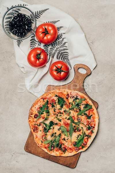 Delicious pizza on wooden cutting board and tomatoes on light background Stock photo © LightFieldStudios