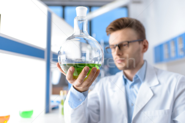 scientist showing laboratory tube, focus on foreground  Stock photo © LightFieldStudios
