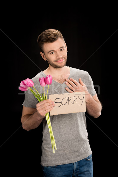 portrait of smiling man holding tulips bouquet and sorry sign on black Stock photo © LightFieldStudios