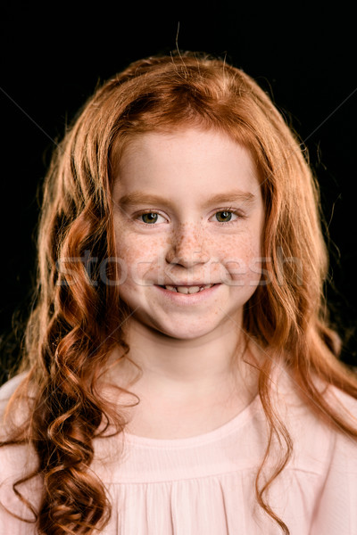 portrait of adorable redhead girl smiling and looking at camera isolated on black Stock photo © LightFieldStudios