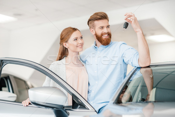 Happy couple holding car key and standing at car in dealership salon    Stock photo © LightFieldStudios