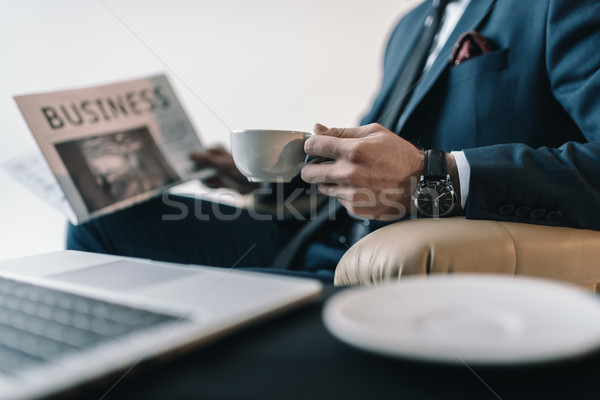 partial view of businessman with cup of coffee reading newspaper in office Stock photo © LightFieldStudios