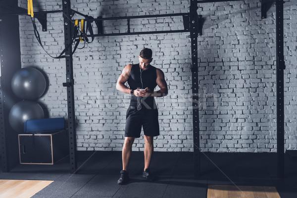 спортивный человека смартфон молодым человеком спортзал Сток-фото © LightFieldStudios
