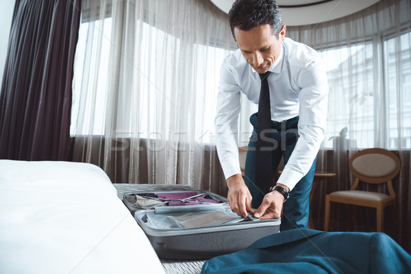 Businessman unpacking suitcase Stock photo © LightFieldStudios