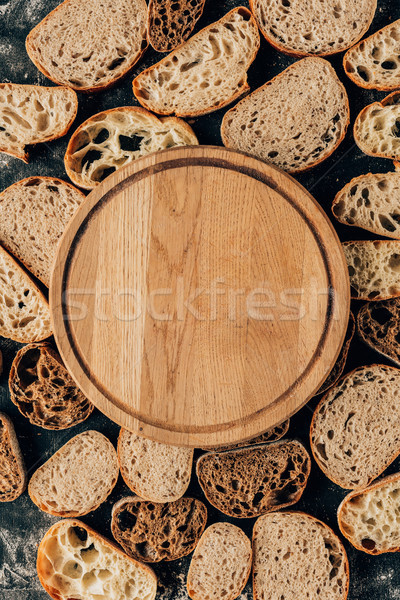 top view of arranged pieces of bread and empty wooden cutting board Stock photo © LightFieldStudios