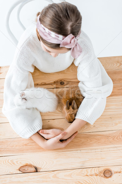 top view of girl sitting at wooden table and looking at cute furry rabbits Stock photo © LightFieldStudios