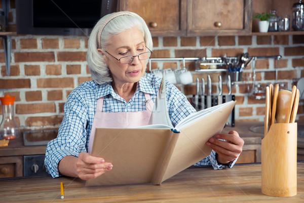 Starszy kobieta książka kucharska okulary czytania kuchnia Zdjęcia stock © LightFieldStudios