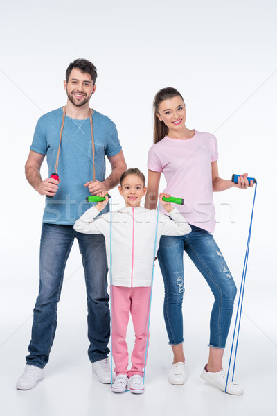 smiling young family with jump ropes on white Stock photo © LightFieldStudios