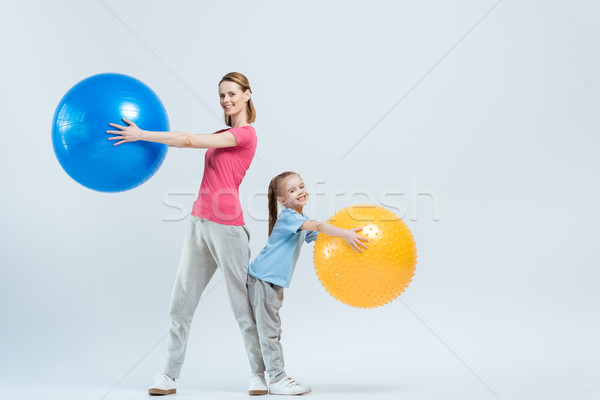 mother and daughter exercising with fitness balls on white Stock photo © LightFieldStudios