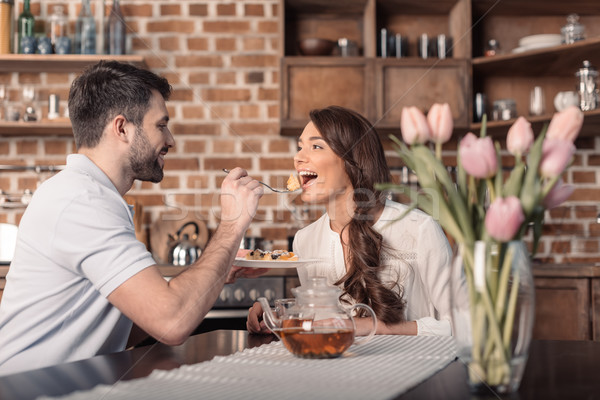 'side view of smiling man feeding woman with cake in kitchen Stock photo © LightFieldStudios