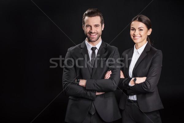 Fiatal mosolyog üzletemberek karok néz kamera Stock fotó © LightFieldStudios