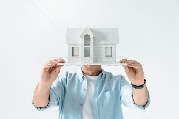 obscure view of man showing house model on white Stock photo © LightFieldStudios