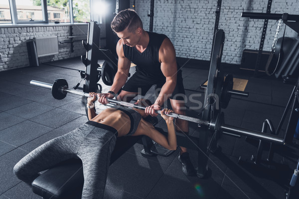 Stock photo: trainer helping woman weightlifting