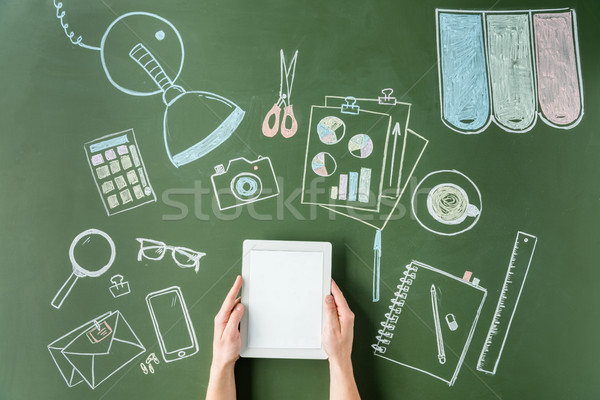 top view of hands holding digital tablet on green board with pictures, small office concept Stock photo © LightFieldStudios