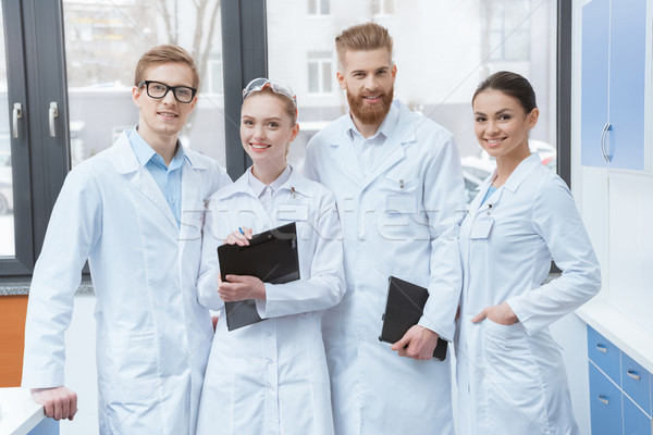 Team of young professional scientists in white coats smiling at camera in laboratory  Stock photo © LightFieldStudios