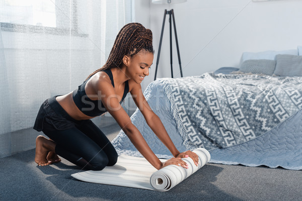 woman rolling out yoga mat Stock photo © LightFieldStudios