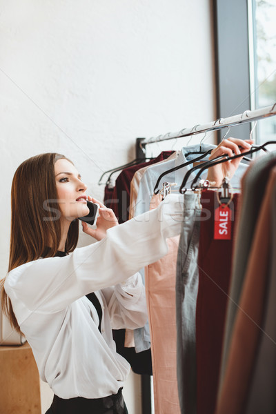 Stock photo: woman with smartphone choosing clothes