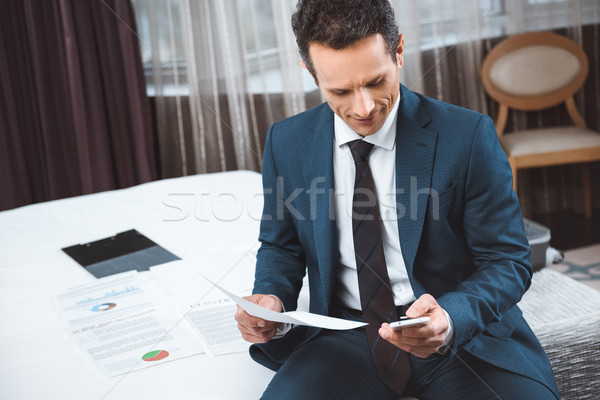 businessman holding paperwork and using smartphone Stock photo © LightFieldStudios