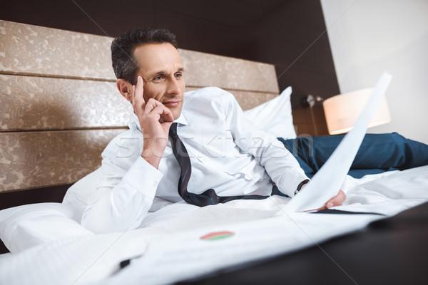 ビジネスマン ベッド 読む 書類 着用 ストックフォト © LightFieldStudios