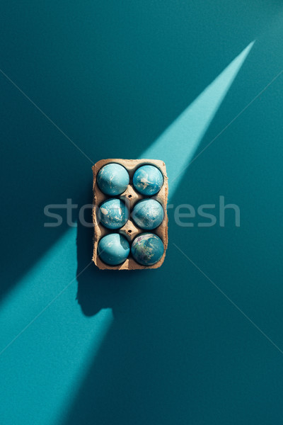 top view of blue easter eggs in tray, on blue with sunbeam Stock photo © LightFieldStudios
