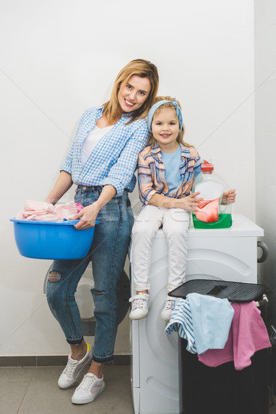 Sonriendo ama de casa lavandería pequeño hija mirando Foto stock © LightFieldStudios