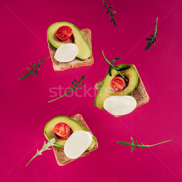 close up view of levitating toasts, pieces of avocado, cherry tomatoes, mozzarella cheese and arugul Stock photo © LightFieldStudios