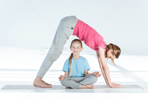 Mother practicing yoga above smiling daughter sitting in lotus position  Stock photo © LightFieldStudios