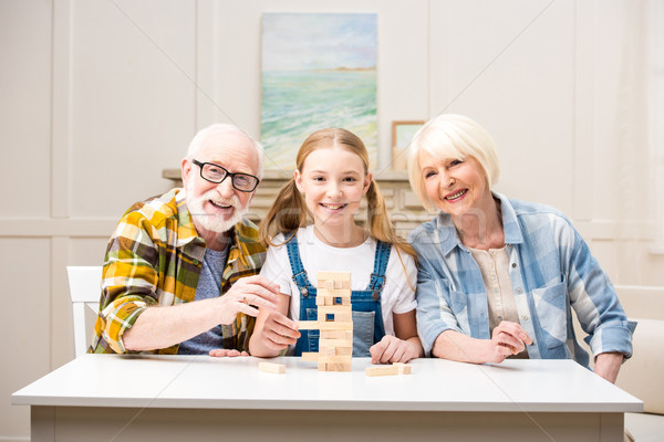 Happy family playing jenga game together and smiling at camera Stock photo © LightFieldStudios