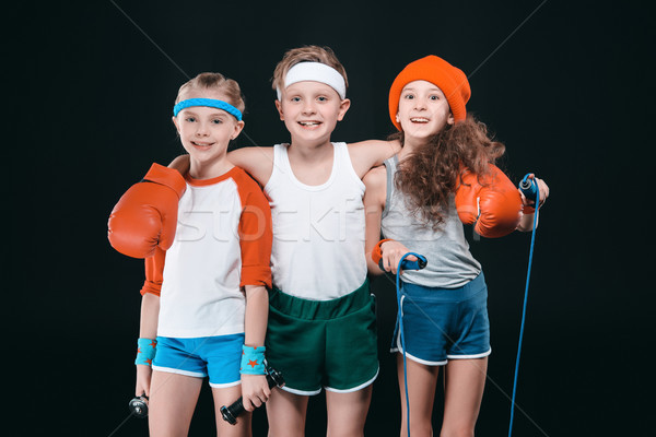 Three smiling kids in sportswear posing with sport equipment and looking at camera Stock photo © LightFieldStudios