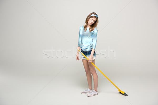 Young woman with broom Stock photo © LightFieldStudios