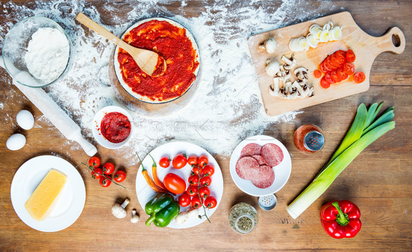 top view of pizza ingredients, tomatoes, salami and mushrooms on wooden tabletop Stock photo © LightFieldStudios