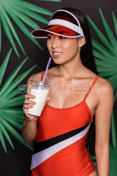 woman in swimsuit and visor drinking milkshake Stock photo © LightFieldStudios