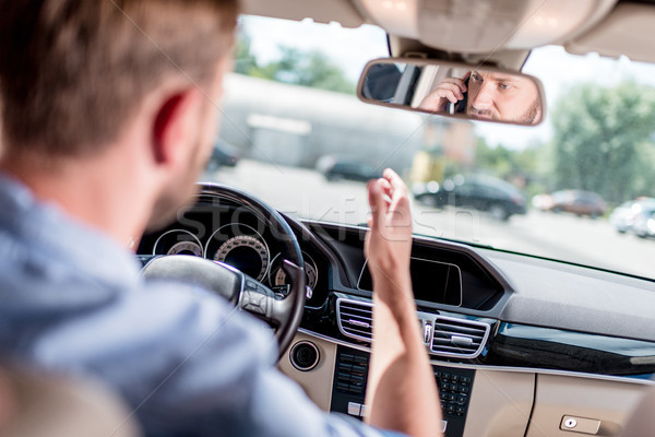 man with smartphone driving car Stock photo © LightFieldStudios