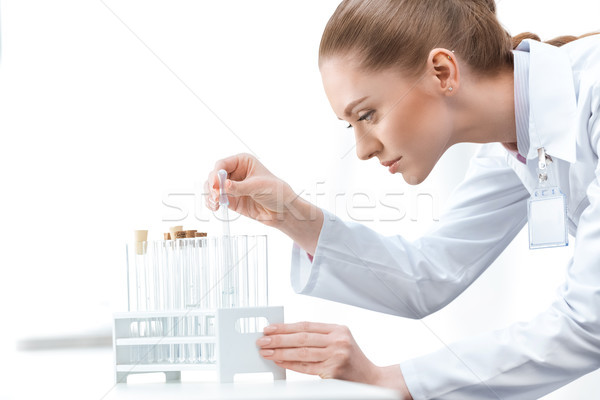 Side view of young woman scientist working with test tubes on white Stock photo © LightFieldStudios