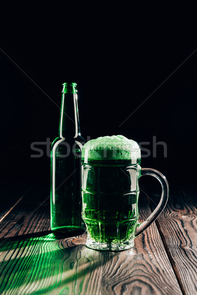 glass and bottle of green beer on wooden tabletop, st patricks day concept Stock photo © LightFieldStudios