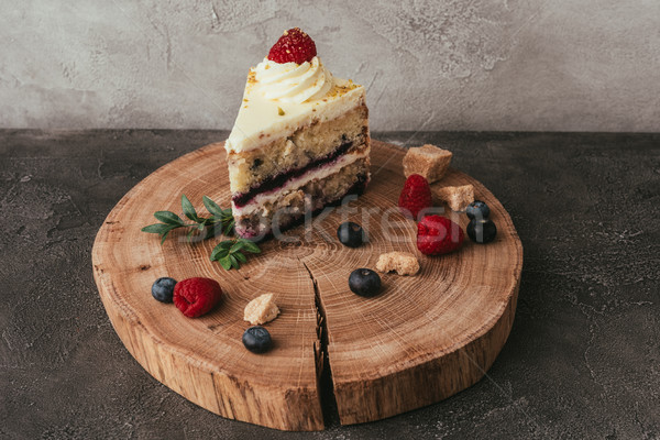 close-up view of sweet tasty cake with whipped cream and berries on wooden board Stock photo © LightFieldStudios