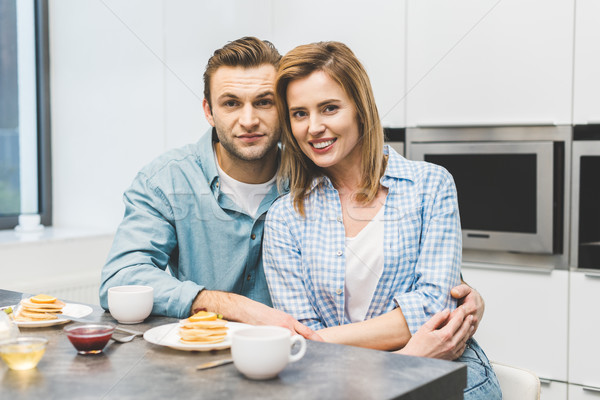 portrait of smiling couple sitting at table with breakfast at home Stock photo © LightFieldStudios