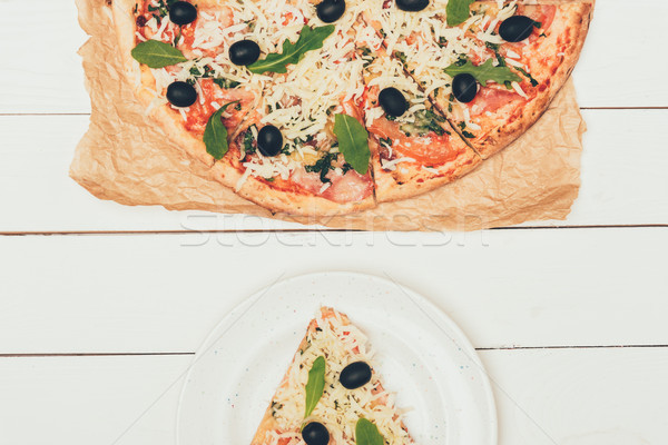 Pizza slice and whole pizza on white wooden background Stock photo © LightFieldStudios