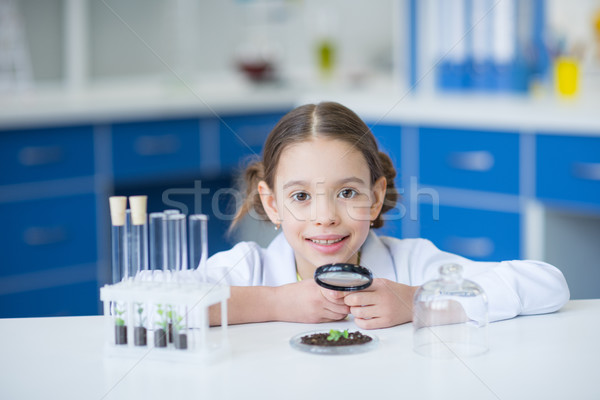 Little girl scientist holding magnifier and working with green plant in soil Stock photo © LightFieldStudios