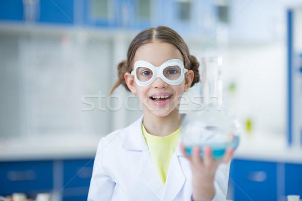 Kislány tudós szemüveg tart flaska mosolyog Stock fotó © LightFieldStudios