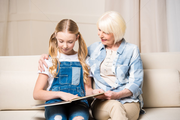Happy grandmother and granddaughter sitting on sofa and looking at photo album Stock photo © LightFieldStudios