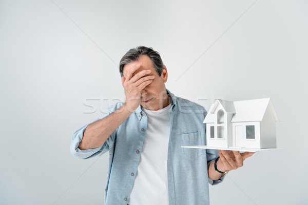 portrait of upset mature man holding house model on grey Stock photo © LightFieldStudios